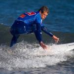 """mavi dalış kıyafetli adam dalga üstünde sörf yapıyor."""