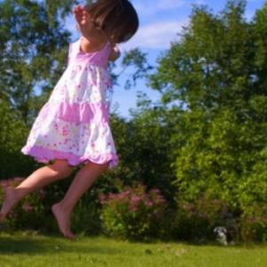 """""""pembe kıyafetli kız havada zıplıyor."""""""